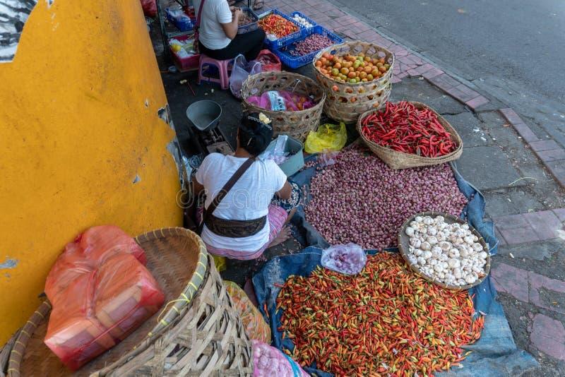 Продавцы специй как красный chili, красный лук и чеснок продают их торговлю в одном угле традиционного рынка Badung стоковая фотография
