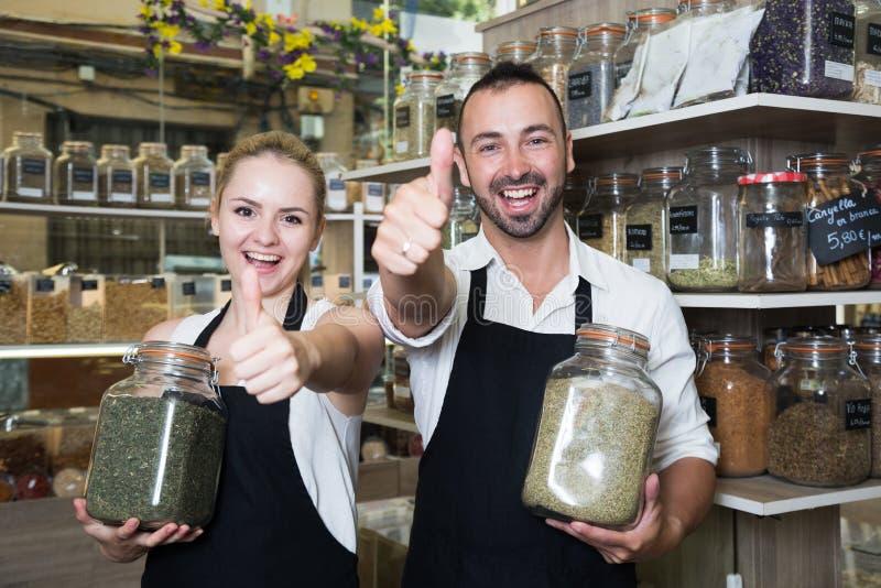 Продавцы человека и женщины представляя с банками высушенных трав в магазине стоковое изображение
