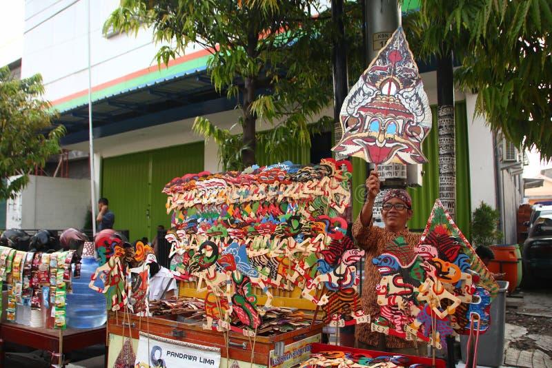 Продавцы Wayang Kulit на улицах, пока показывающ их продавая продукты в Tegal/центральной Ява, Индонезия, стоковые фотографии rf