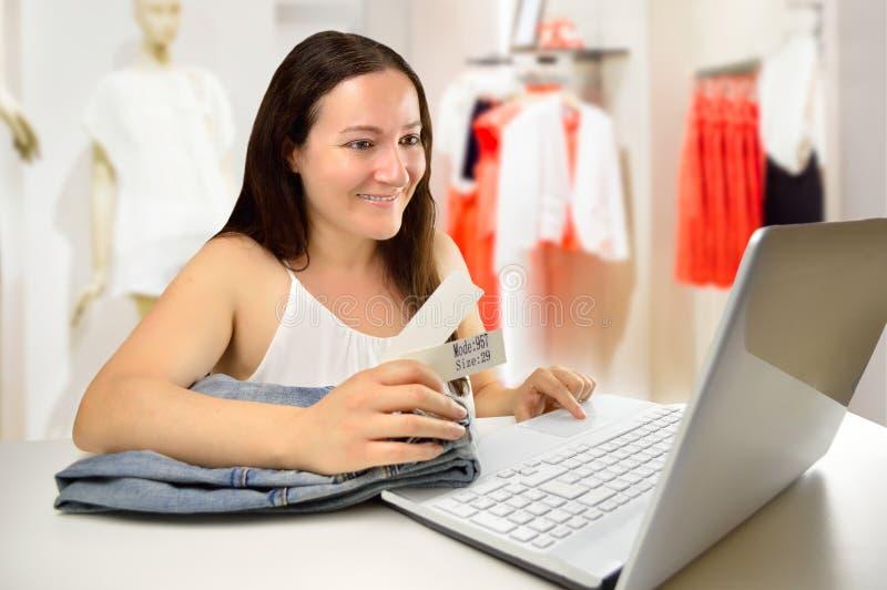 Продавщица работая с компьтер-книжкой стоковое фото
