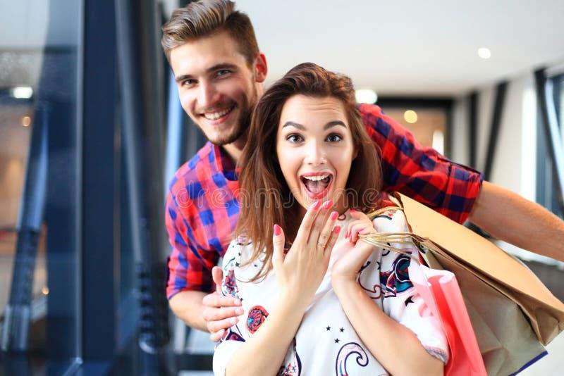 Продажа, защита интересов потребителя и концепция людей - счастливая молодая пара при хозяйственные сумки идя в мол стоковые изображения rf