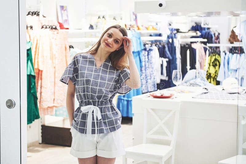 Продажа, мода, защита интересов потребителя и концепция людей - счастливая молодая женщина с хозяйственными сумками выбирая одежд стоковое фото rf