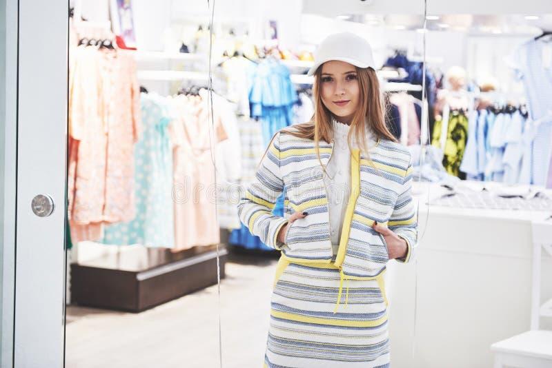 Продажа, мода, защита интересов потребителя и концепция людей - счастливая молодая женщина с хозяйственными сумками выбирая одежд стоковая фотография