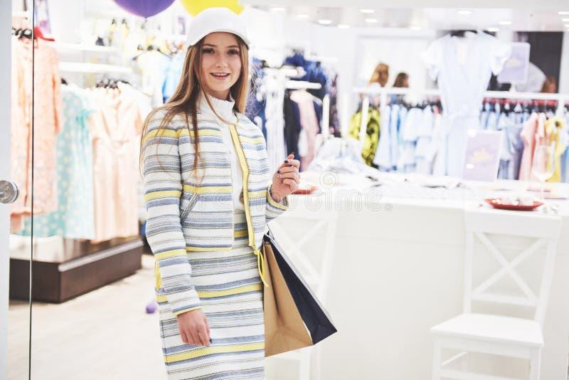 Продажа, мода, защита интересов потребителя и концепция людей - счастливая молодая женщина с хозяйственными сумками выбирая одежд стоковое изображение rf