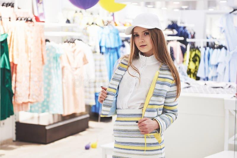 Продажа, мода, защита интересов потребителя и концепция людей - счастливая молодая женщина с хозяйственными сумками выбирая одежд стоковая фотография rf
