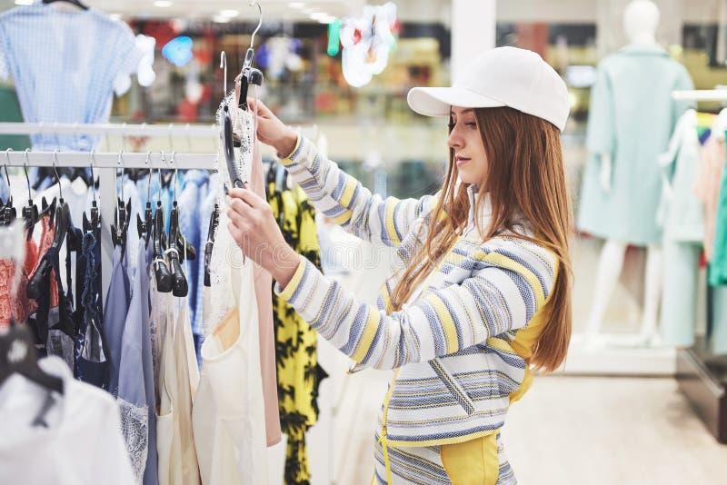 Продажа, мода, защита интересов потребителя и концепция людей - счастливая молодая женщина с хозяйственными сумками выбирая одежд стоковые фотографии rf