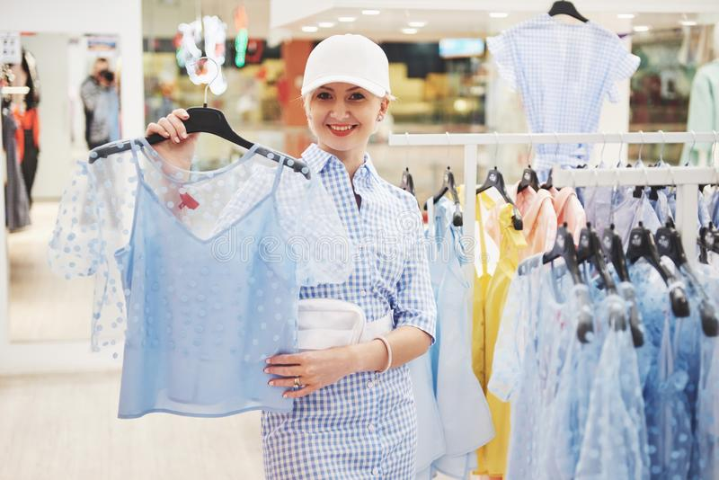 Продажа, мода, защита интересов потребителя и концепция людей - счастливая молодая женщина с хозяйственными сумками выбирая одежд стоковые фото