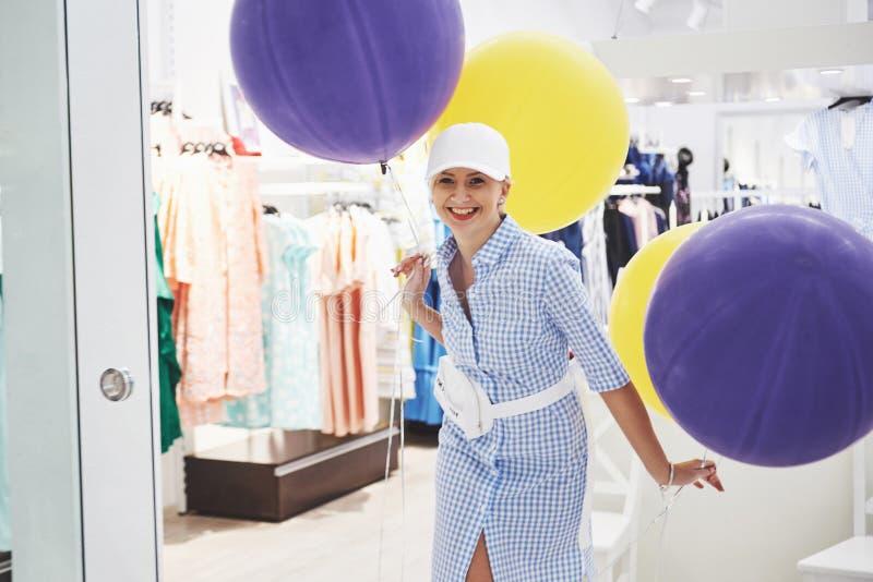 Продажа, мода, защита интересов потребителя и концепция людей - счастливая молодая женщина с хозяйственными сумками выбирая одежд стоковые изображения rf