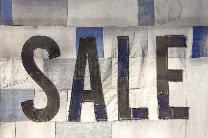 Продажа сезона, черная пятница и творческая ходя по магазинам концепция Знак продажи сделанный из джинсовой ткани стоковая фотография rf