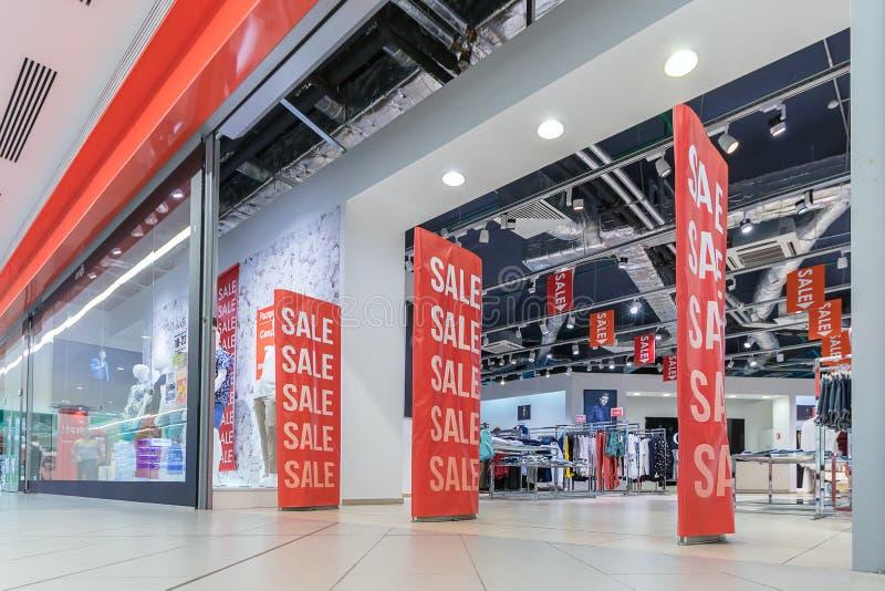 Продажа сезона, черная пятница и ходя по магазинам концепция ворота датчика Анти--похищения на входе к магазину одежды с красным  стоковая фотография rf