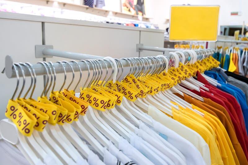 Продажа сезона, черная пятница и ходя по магазинам концепция Желтые ленты со знаком процентов вокруг вешалок в розничном магазине стоковое изображение rf