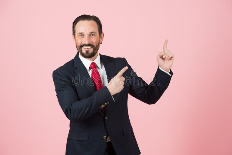 Продажи укомплектовывают личным составом указывать вверх пальцами на розовой предпосылке Человек в костюме рекламирует вверх по м стоковые фото