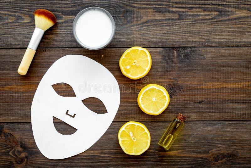 Продукты курорта стороны Лицевая маска, сливк, масло, чистит щеткой около кусков лимона на темном деревянном космосе экземпляра в стоковое фото