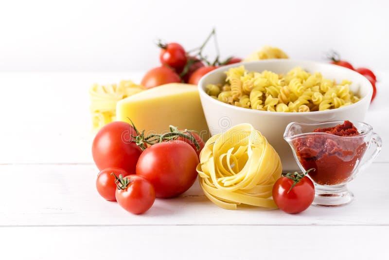 Продукты макаронных изделий с еды ингридиентов Fettuccine Fusili макаронных изделий сыра томата концом предпосылки сырцовой италь стоковые фото