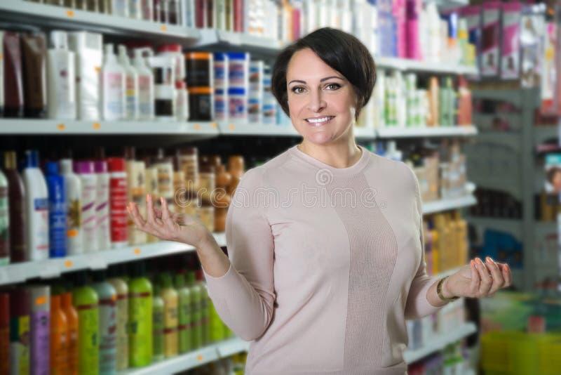 Продукты ухода за волосами элегантной женщины покупая стоковые изображения