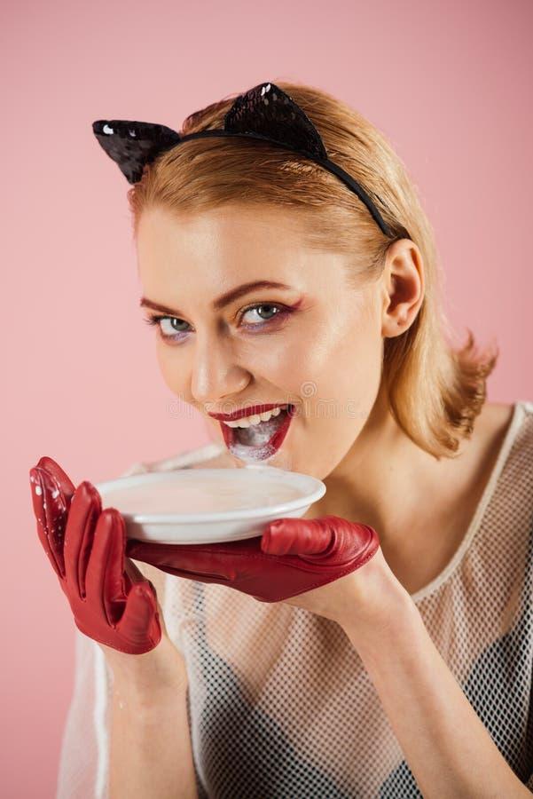 Продукт и вереск экологичности Девушка в ушах котенка и красных перчатках с югуртом на розовой предпосылке Женщина кота ест смета стоковое фото rf