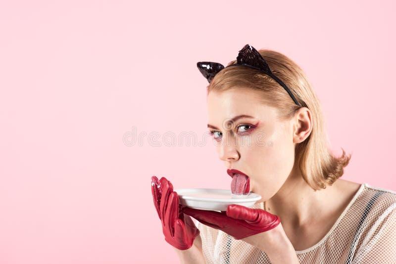 Продукт и вереск экологичности Женщина кота ест сметану Девушка в ушах котенка и красных перчатках с югуртом на розовой предпосыл стоковая фотография