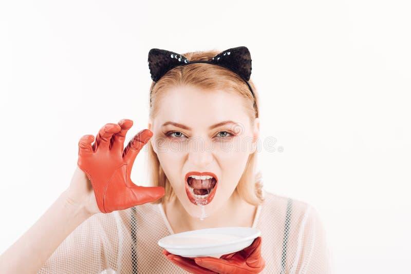 Продукт и вереск экологичности Женщина кота ест сметану Девушка в ушах котенка и красных перчатках при югурт изолированный на бел стоковые изображения
