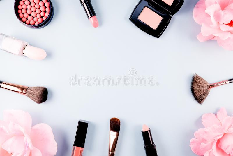 Продукт макияжа предпосылки красоты косметический, с зелеными лист и розовым розовым цветением на пурпурной предпосылке весны ден стоковое фото rf