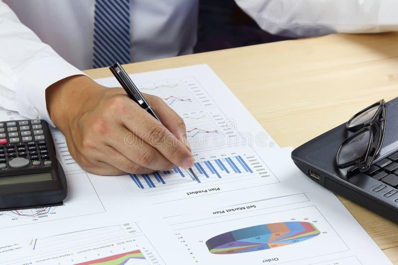 Продукт отчетного доклада и плана бизнесмена анализируя se денег стоковые фото