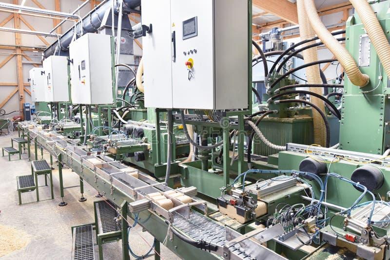 Продукция деревянных лепешек в фабрике и sawm обработки древесины стоковые фотографии rf