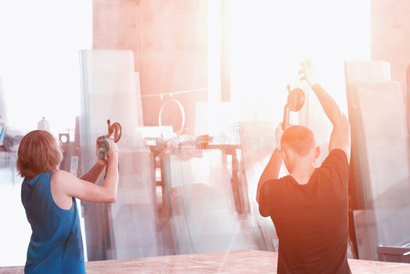 Продукция окон pvc, работников на чашках всасывания переносит стекло для продукции стеклопакетов, рабочего класса стоковое изображение rf