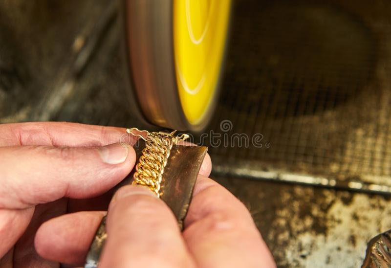Продукция ювелирных изделий Ювелир полирует браслет золота стоковое фото