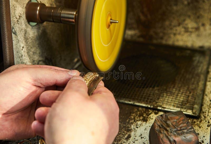 Продукция ювелирных изделий Ювелир полирует браслет золота стоковые фото