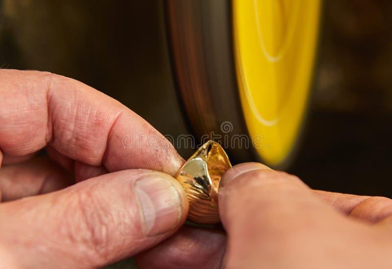 Продукция ювелирных изделий Ювелир полирует кольцо золота на шлифовальном приборе стоковое фото rf