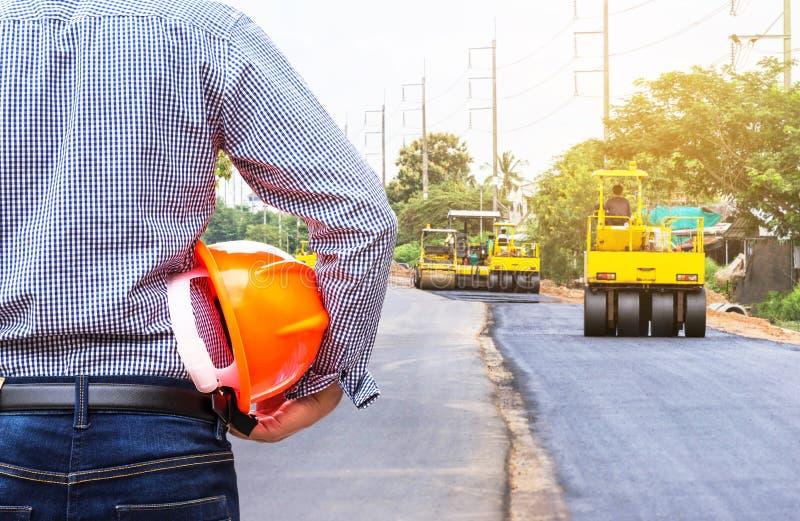 Проектируйте держать шлем безопасности на месте строительства дорог с дорогой асфальта compactor ролика работая стоковое фото rf