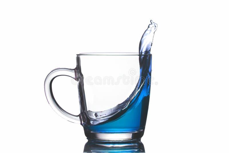 Прозрачная кружка с голубой жидкостью лить вне, изолят, конец-вверх стоковые фотографии rf