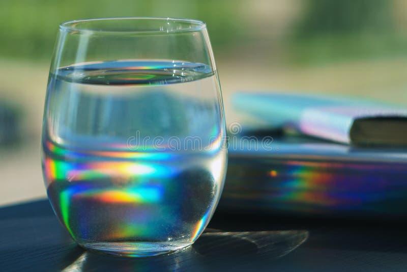 Прозрачное стекло заполненное с пятнами радуги воды отражая от тетради в голографической крышке стоковое фото rf
