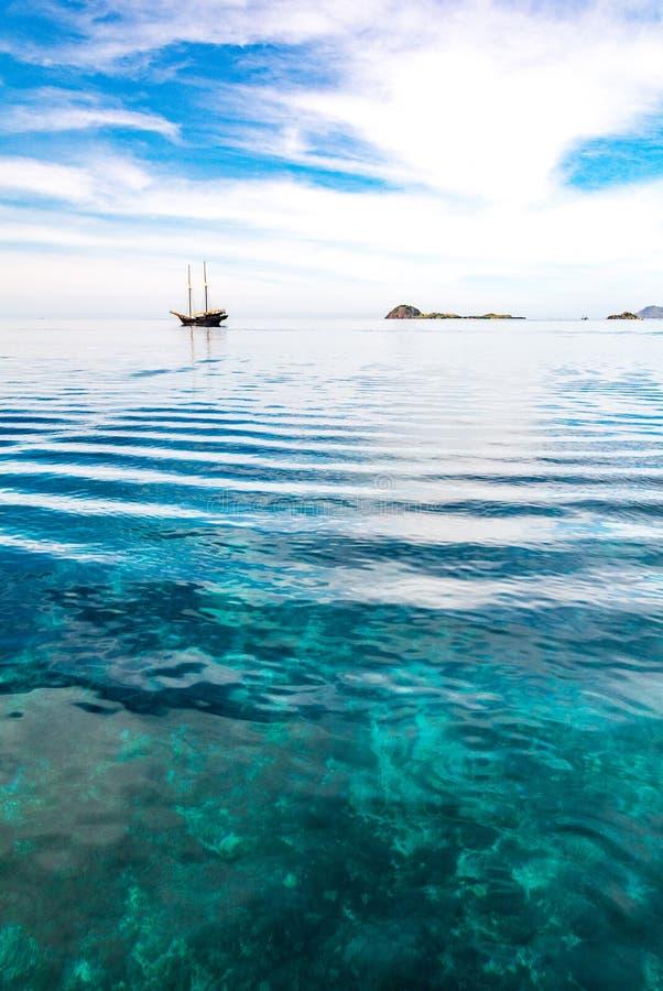 Прозрачное темносинее море и туристская шлюпка стоковое фото