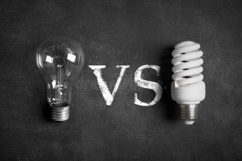 Прозрачные и белые (энергосберегающие) электрические лампочки ПРОТИВ концепции стоковые фото