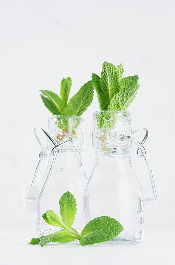 Прозрачный лимонад с sprig мяты в винтажных бутылках на мягкой белой деревянной предпосылке стоковые фото