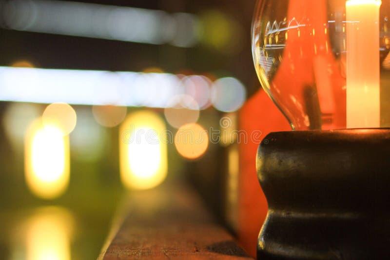 Прозрачный стеклянный держатель для свечи, темное деревянное основание, установил на деревянном столе стоковые изображения rf