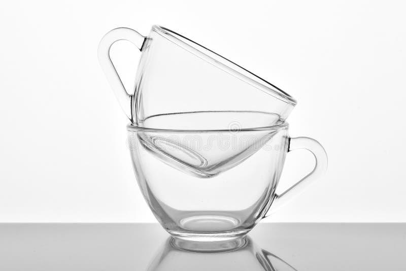 2 прозрачных стеклянных чашки на белой предпосылке стоковое фото rf