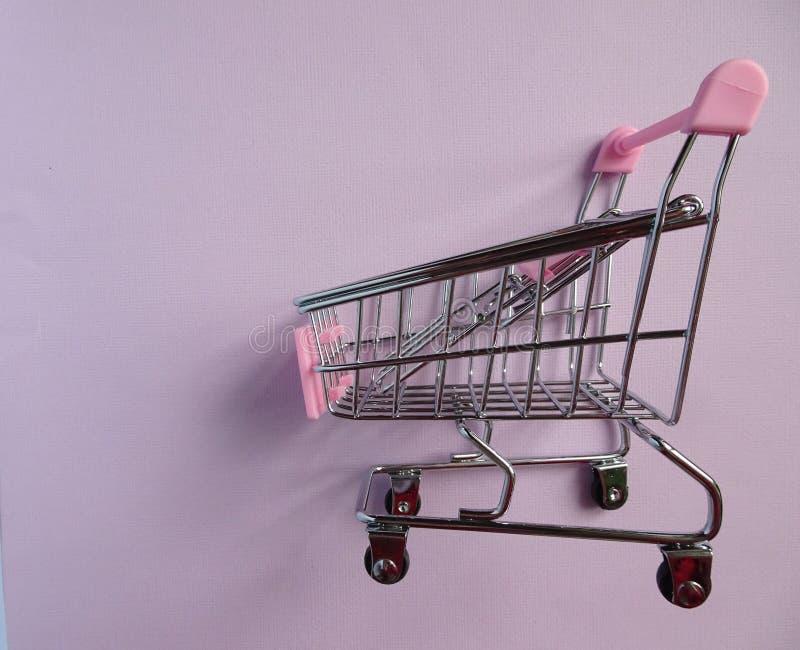 произведенная тележкой покупка изображения 3d Пустая вагонетка супермаркета на фиолетовой предпосылке Взгляд со стороны стоковые фото