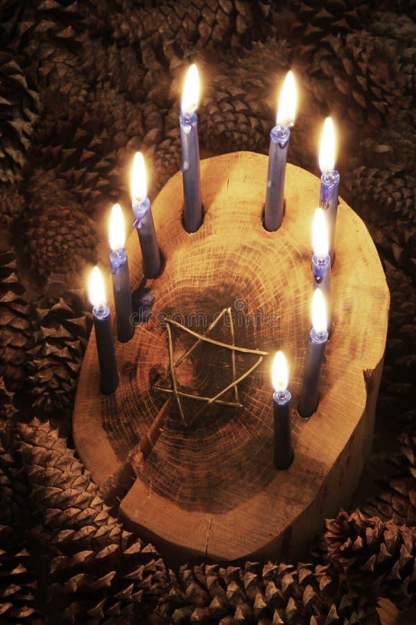 Произведенное деревенское деревянное menorah журнала окруженное конусами сосны с звездой inset Дэвида, освещенных свечей стоковые фото