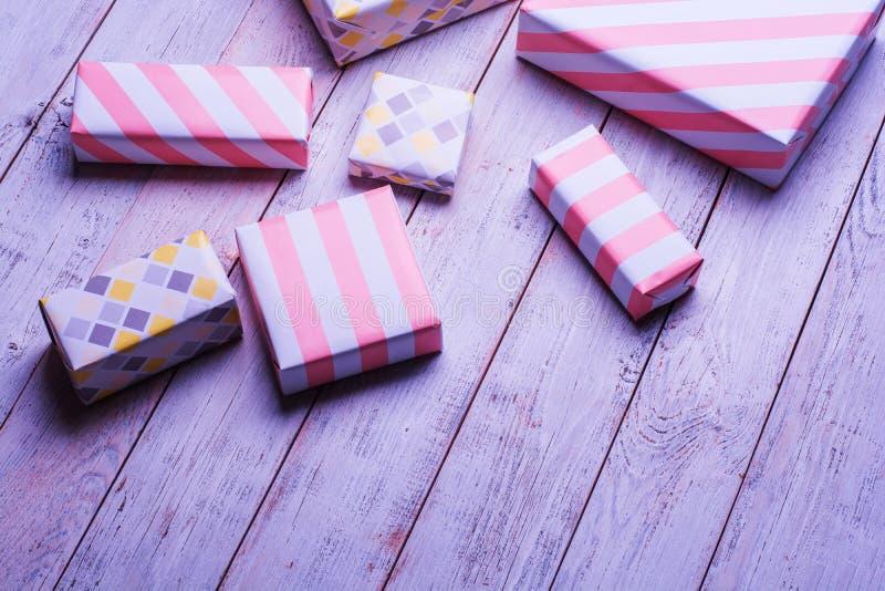 Произведите бумажные присутствующие коробки на деревянной предпосылке с космосом экземпляра, цветные поглотители в мягком цвете стоковое фото