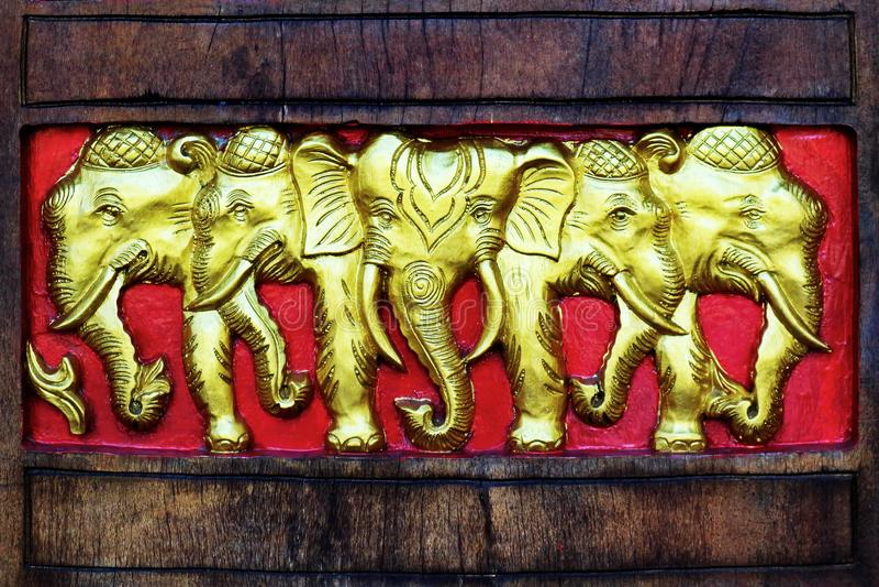 Производить золотых слонов деревянный стоковое фото