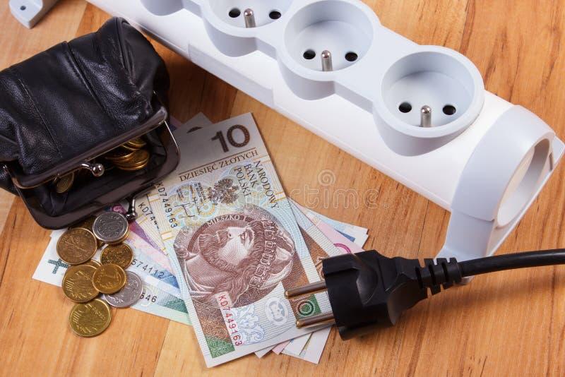 Прокладка электропитания с disconnected штепсельной вилкой и деньгами валюты заполированности, стоимостями энергии стоковое фото