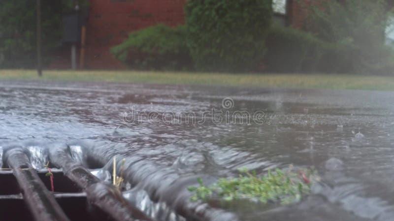 Проливной дождь падая на улицу и пропуская через сток сточной трубы стоковые изображения rf
