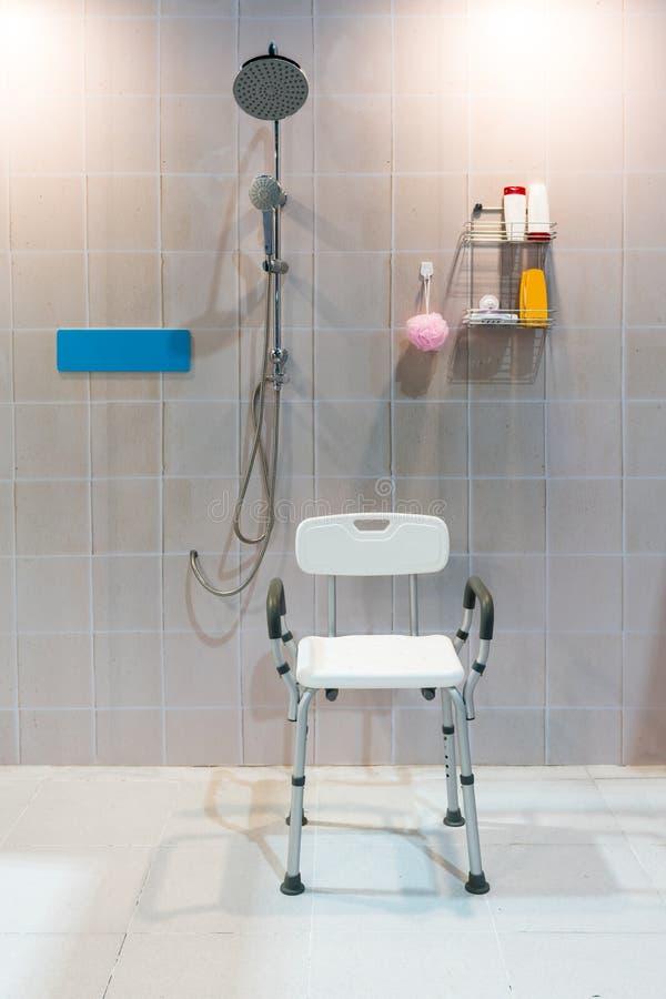 Проложенный стул ливня с оружиями и задняя часть в ванной комнате с ярким t стоковые фотографии rf