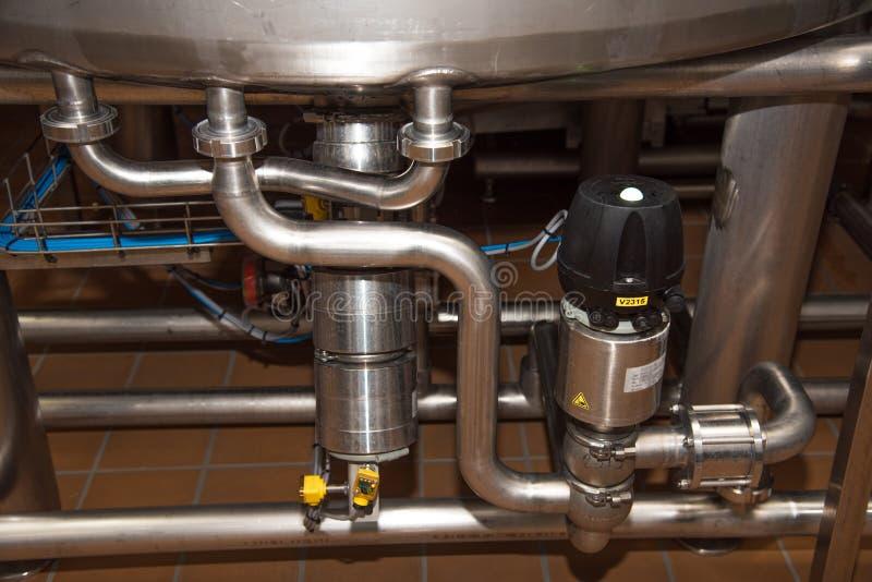Промежуточные трубы под большими чонсервными банками на современном заводе для produc стоковые изображения