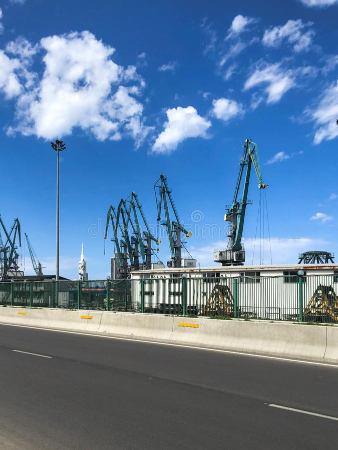 Промышленная верфь для кораблей в порте с большими кранами утюга для нагружать и разгружать грузы около дороги стоковая фотография