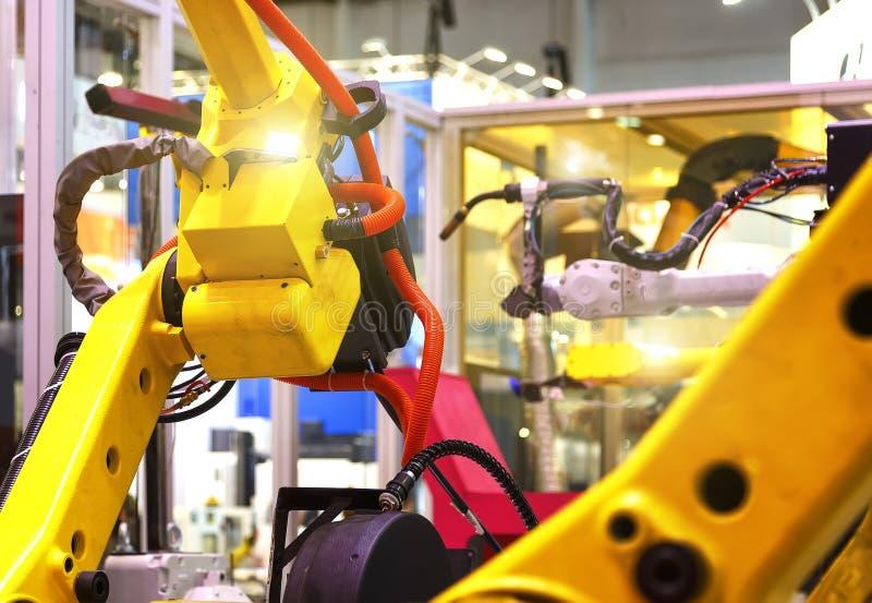Промышленная линия с желтыми роботами на сторонах, продукции и обрабатывать частей металла, slective фокусе стоковые фотографии rf