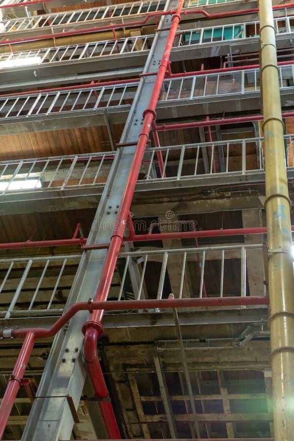 Промышленная предпосылка, старая получившаяся отказ зала фабрики с лестницами и свет дня стоковая фотография rf