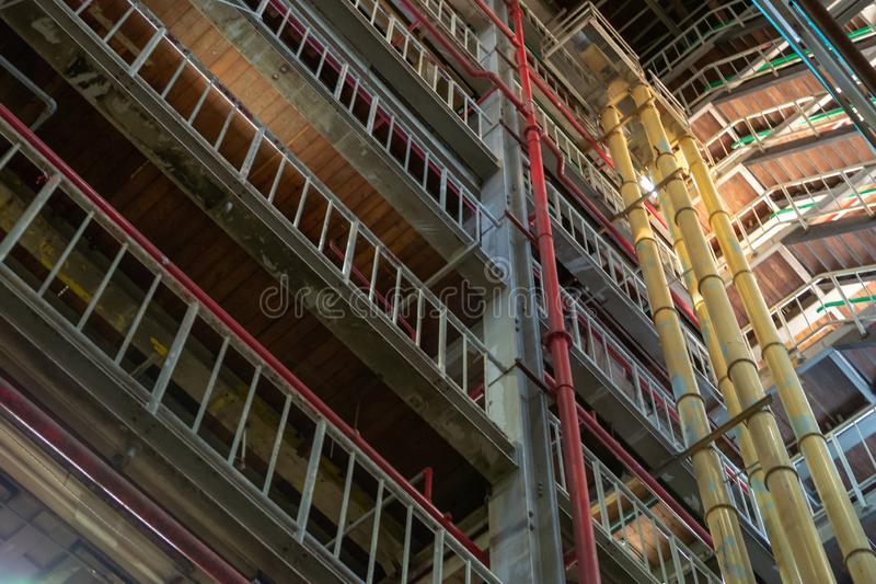 Промышленная предпосылка, старая получившаяся отказ зала фабрики с лестницами и свет дня стоковые фотографии rf