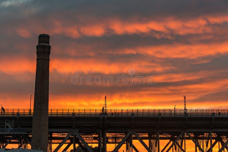 Промышленные силуэты архитектуры против яркого неба на предпосылке стоковое фото